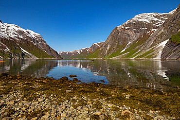 Snow capped mountains reflected in the still waters of the fjord where kayakers are enjoying the view, Nordfjord, Norway, Scandinavia, Europe