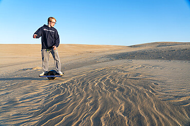 Christopher Brown rides his One-Wheel across a sand dune in Nags Head, North Carolina