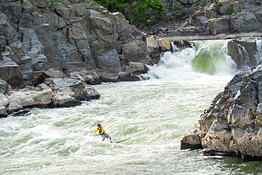 Ian Brown stand up paddle surfs challenging whitewater below Great Falls of the Potomac River, USA. MR