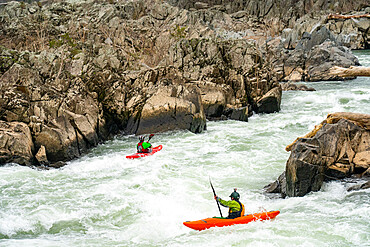 Whitewater kayakers run the last drop of the Fishladder on the Great Falls of the Potomac River, Maryland USA. MR