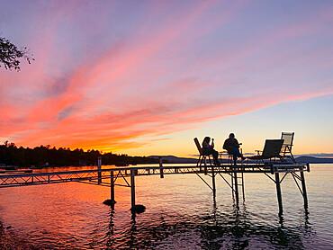 Mother and daughter play ukulele's together on a dock over Sebago Lake, Maine USA. MR on file - Lily Brown, Jennifer Jordan