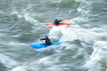 A kayaker surfs big standing waves of the Potomac River near Great Falls in his whitewater boat Virginia USA. MR Ian Brown