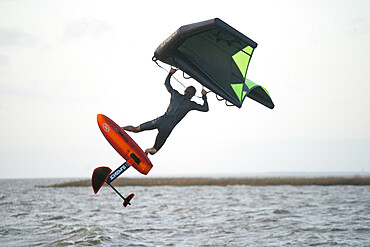 Pro surfer James Jenkins jumps his wing surfer over the Pamlico Sound at Nags Head, North Carolina USA. MR - 1343-122