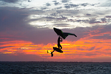 Pro surfer James Jenkins jumps his wing surfer at sunset over the Pamlico Sound at Nags Head, North Carolina, United States of America, North America