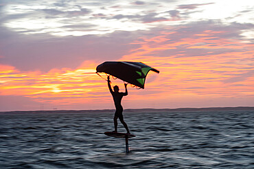 Pro surfer James Jenkins on his wing surfer flies across the Pamlico Sound at Nags Head, North Carolina USA. MR - 1343-125