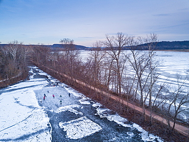 Ice skaters in a pond hockey game on the frozen C&O canal next to the Potomac River