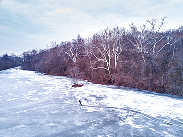A man and his dog ice skates on a path across frozen pond in winter