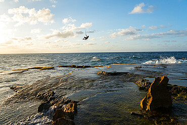 A kiteboarder jumps high over rocks at Montones, Puerto Rico. MR