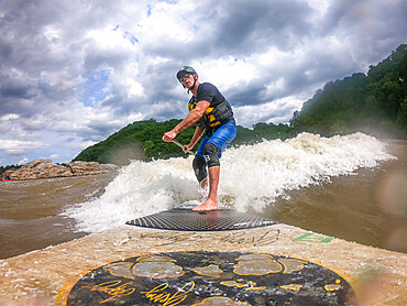 Photographer Skip Brown stand up paddle surfs a challenging whitewater wave on the Potomac River, USA. MR