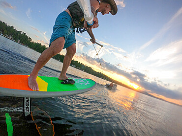 Photographer Skip Brown foils behind a small boat at sunset on Sebago Lake, Maine USA. MR
