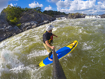 Skip Brown surfs his stand up paddleboard in fast moving whitewater on the Potomac River near Great Falls, Virginia MR