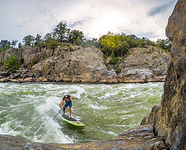 Skip surfs Odeck wave below Great Falls on the Potomac River, Virginia