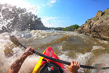 Photographer Skip Brown surfs his kayak on a whitewater wave on the Potomac River Virginia/Maryland USA. MR