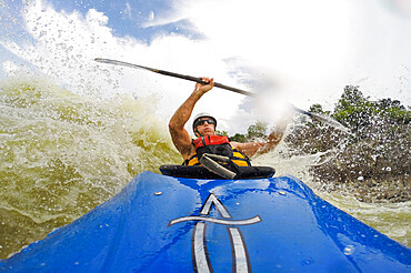 Photographer Skip Brown surfs his whitewater kayak through big water on the Potomac River below Great Falls. Virginia USA MR
