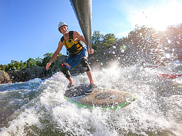 Photographer Skip Brown stand up paddle surfs challenging whitewater below Great Falls of the Potomac River, USA. MR