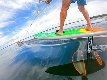 Photographer Skip Brown rides his hydrofoil behind a small boat at on Sebago Lake, Maine, United States of America, North America