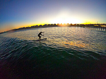 Stand up paddle boarder catches a wave at sunset Nags Head, North Carolina USA