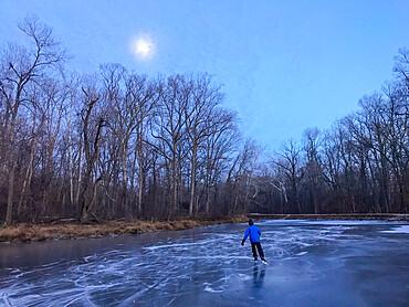 Man skates the frozen C&O Canal under a hazy full moon. Potomac, Maryland USA