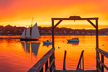 A schooner returns to dock at sunset at Bailey Island, Casco Bay, Maine, USA