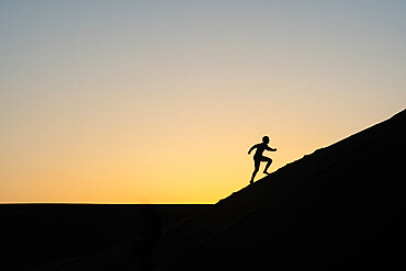 Sillouette of man running up a sand dune in Nags Head, North Carolina USA.