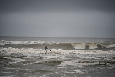 Man trying to get out through big shorebreak on his stand up paddle board. Nags Head, NC - 1343-78