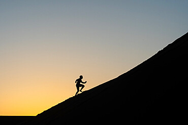 Silhouette of a man running up a sand dune in Nags Head, North Carolina, United States of America, North America