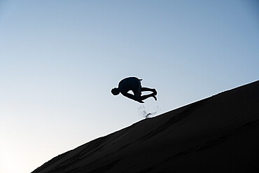 Sillouette of man tumbling down a sand dune in Nags Head, North Carolina USA.