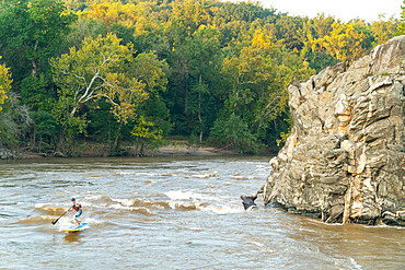 Ian Brown stand up paddle surfs a whitewater wave on the Potomac River near Potomac, Maryland USA MR