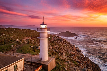 Aerial sea landscape view of Cape Tourinan Lighthouse at sunset with pink clouds, Galicia, Spain