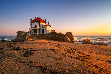 Beautiful chapel Capela do Senhor da Pedra on the beach at sunset in Miramar, in Portugal
