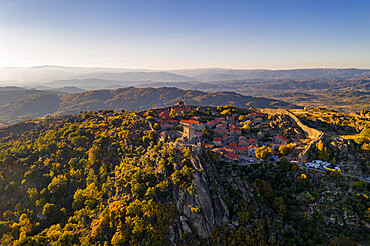 Drone aerial panorama of historic village of Sortelha with castle and with turbines on natural landscape, Centro, Portugal, Europe