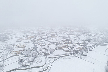Drone aerial view of a road and remote village covered with snow in the North of Portugal, Vila Real