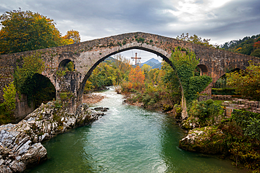 Cangas de Onis historic medieval roman bridge with Sella river in Picos de Europa national park, Spain