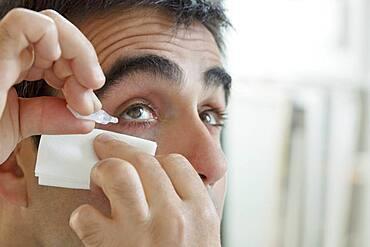 Man using eye lotion