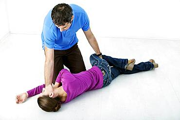 First aid techniques : placing the victim in the recovery position. Step 4 : roll the victim by pulling on their leg until their knee touches the ground. Remove your hand from the victim's head, holding their elbow so their hand stays in place.