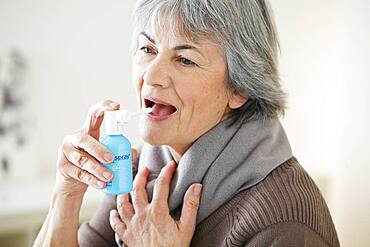 Elderly person using mouth spray