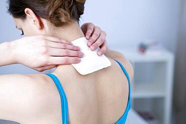 Woman applying heat patch.