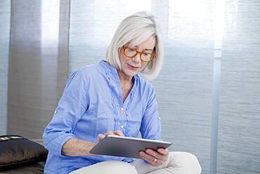 Senior woman using tablet computer.