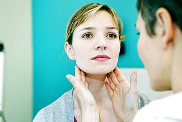 Woman palpating lymph node