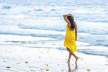 Woman walking on beach at Magdalena Grand Beach Resort on the island of Tobago; Trinidad and Tobago.
