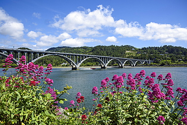 Isaac Lee Patterson Bridge on the Rogue River, with a jet boat passing under; from Jot's Resort in Gold Beach on the southern Oregon coast.