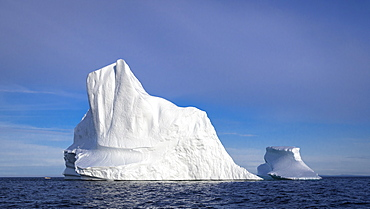 Iceberg off the coast of Newfoundland, Canada. With fishing boat at left for scale.