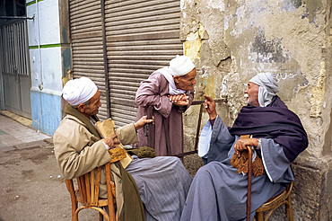 Three old men outside talking in a street in Cairo, Egypt, North Africa, Africa
