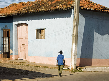 A man walking past colourfully painted houses in Trinidad, UNESCO World Heritage Site, Cuba, West Indies, Central America