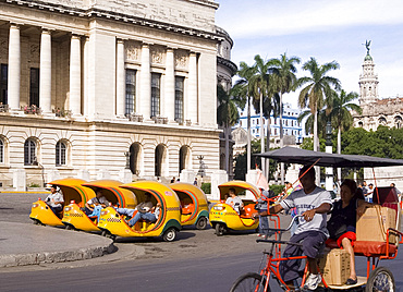 A rickshaw passing 'coco' taxis in central Havana, Cuba, West Indies, Central America