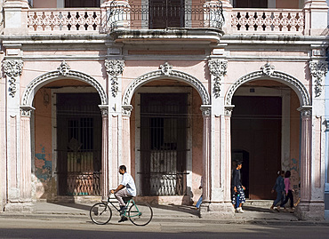 A cyclist passing an ornate old building on Avenida Reina in central Havana, Cuba, West Indies, Central America