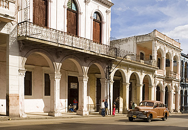 A vintage American car coming along Avenida Reina in central Havana, Cuba, West Indies, Central America