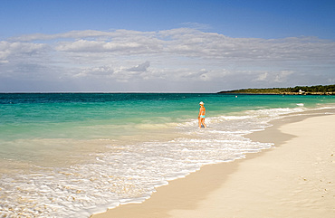 A woman walking in the surf at Playa Esmeralda, Carretera Guardalavarca, Cuba, West Indies, Central America