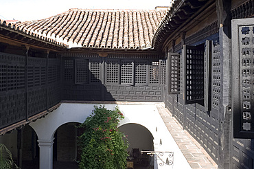 An interior courtyard surrounded by Moorish style wooden screens at the Casa de Diego Velazquez (Museo de Ambiente Historico Cubano), Santiago de Cuba, Cuba, West Indies, Central America
