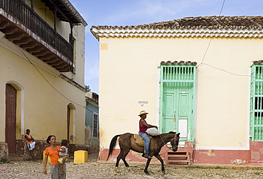 A cowboy riding a horse through the cobbled streets and a woman carrying her baby, Trinidad, Cuba, West Indies, Central America